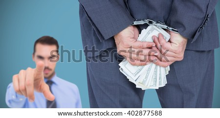 Rear view of businessman with handcuff and money against grey background - stock photo