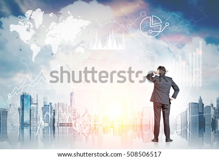 Rear view of businessman with paper cup of coffee standing and looking at large city panorama. Graphs are floating in the air. Toned image. Elements of this image furnished by NASA