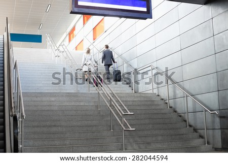 Rear view of businesspeople with luggage moving upstairs in railroad station - stock photo