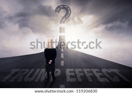 Rear view of businessperson with cardboard head, standing on the road while looking at question mark with Trump Effect word on the asphalt