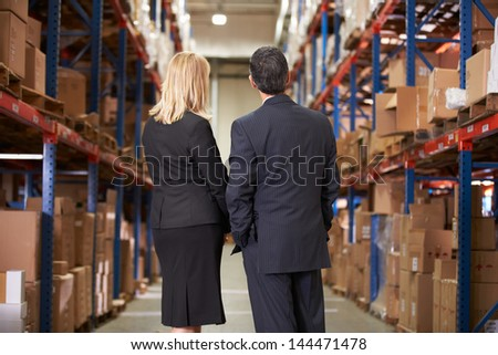 Rear View Of Businesswoman And Businessman In Warehouse - stock photo