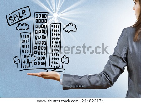 Rear view of businesswoman holding sketch of building in palm - stock photo