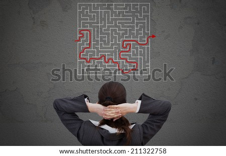 Rear view of businesswoman looking at solved maze drawn on wall - stock photo