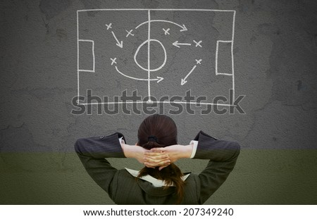 Rear view of businesswoman looking strategically game plan drawn on wall
