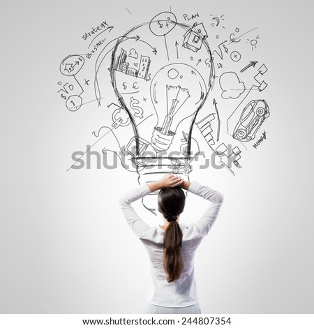 Rear view of businesswoman looking thoughtfully at business sketches