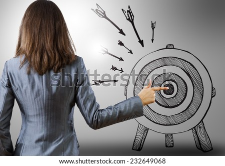Rear view of businesswoman pointing at drawn target - stock photo