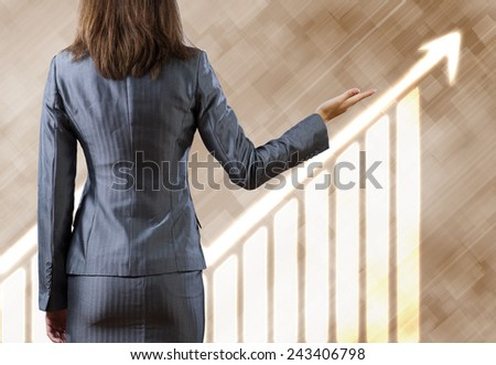 Rear view of businesswoman pointing at growth graph - stock photo