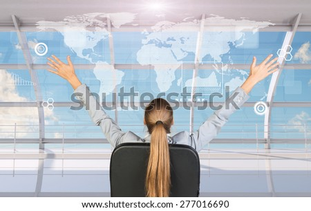 Rear view of businesswoman sitting in chair with arms up in front of window with virtual world map