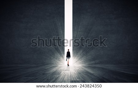 Rear view of businesswoman standing in light of crack in wall - stock photo