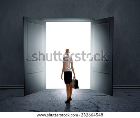 Rear view of businesswoman standing in light of opened door - stock photo