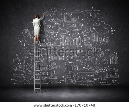 Rear view of businesswoman standing on ladder and drawing business sketch on wall - stock photo