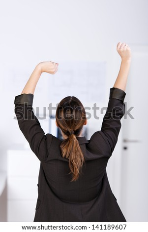 Rear view of businesswoman stretching in office
