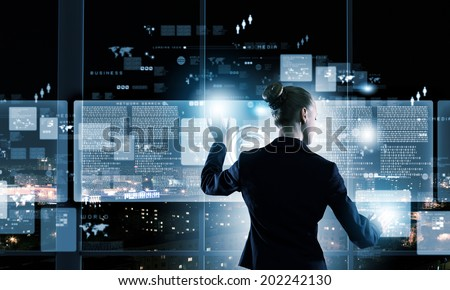 Rear view of businesswoman touching icon of digital screen