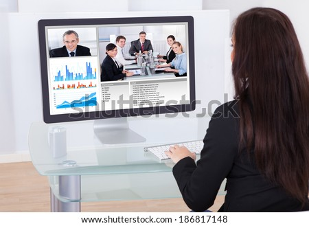 Rear view of businesswoman using having video conference in office - stock photo