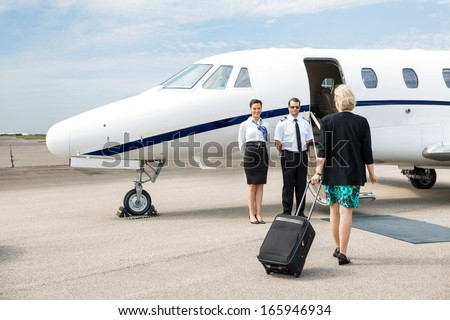 Rear view of businesswoman with luggage walking towards private jet while pilot and airhostess standing by - stock photo