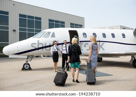 Rear view of businesswomen with luggage walking towards private jet while pilot and airhostess standing by - stock photo