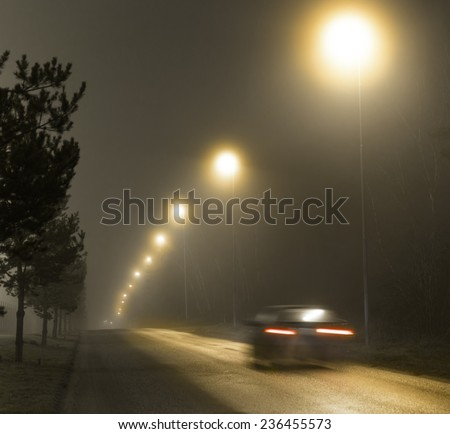 Rear view of car in blurred motion on country road on foggy night