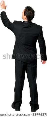 Rear view of Caucasian man with short black hair in a tuxedo using holographic interface - Isolated - stock photo