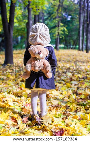 Rear view of charming little girl with a backpack-bear behind in the autumn sunny forest - stock photo