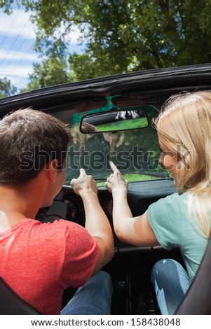 Rear view of cheerful couple pointing ahead while having a ride in cabriolet - stock photo
