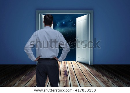 Rear view of classy young businessman posing against door opening in dark room to show sky