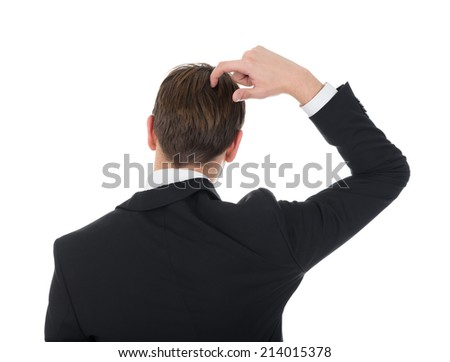 Rear view of confused businessman scratching his head over white background - stock photo