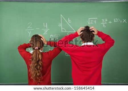 Rear view of confused schoolchildren standing against board in classroom