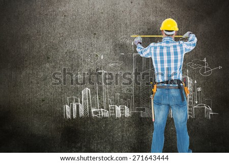 Rear view of construction worker using measure tape against hand drawn city plan - stock photo
