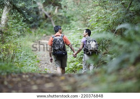 Rear view of couple hiking on trail - stock photo