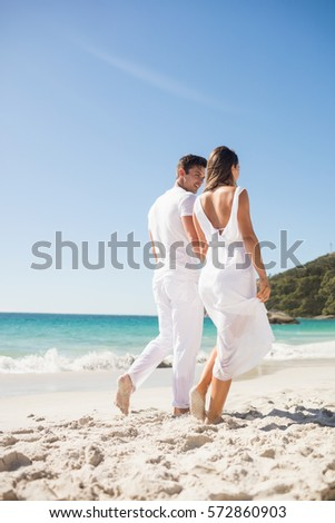 Rear view of couple holding hands on the beach