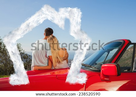 Rear view of couple hugging and admiring panorama against house outline in clouds - stock photo