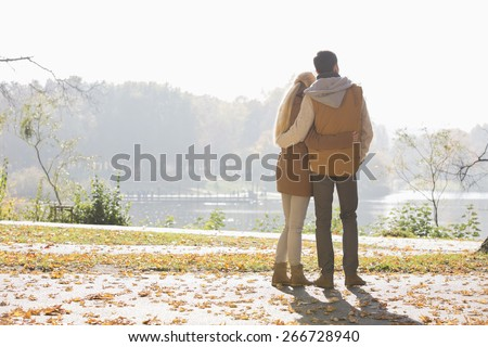 Rear view of couple looking at lake in park during autumn - stock photo