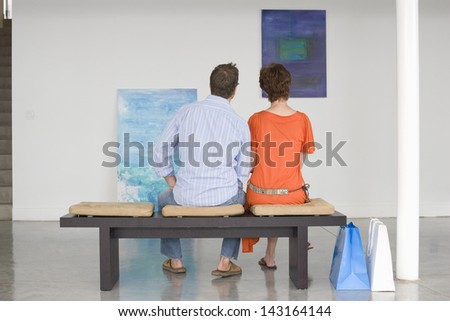 Rear view of couple looking at paintings while sitting on bench in art gallery - stock photo