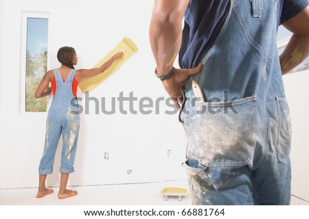 Rear view of couple painting walls - stock photo