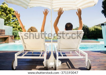 Rear view of couple raising hands and lying on deck chairs poolside