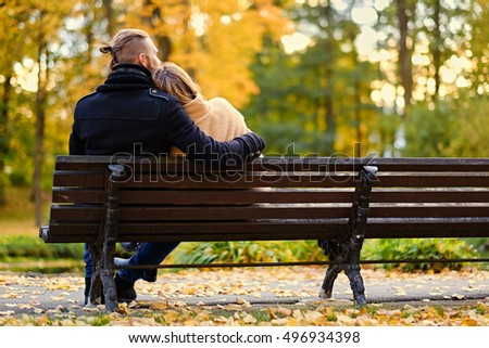 Rear view of couple sits on a bench in an autumn park.