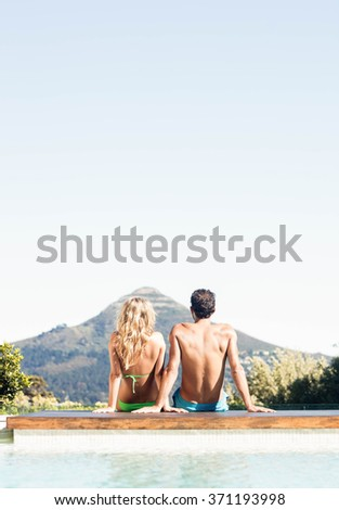 Rear view of couple sitting bu the pool looking at the landscape - stock photo
