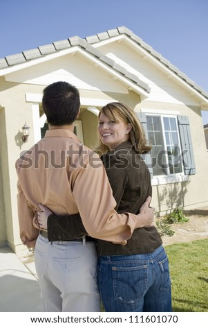 Rear view of couple standing in front of a new home - stock photo