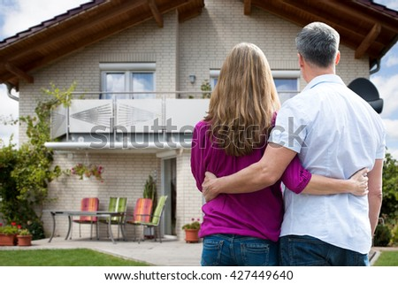 Rear View Of Couple Standing In Front Of Their House