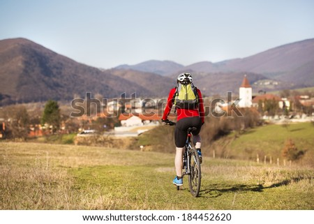 Rear view of cyclist man riding mountain bike on outdoor trail in nature - stock photo