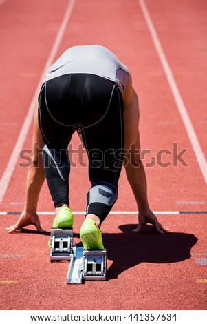 Rear view of determined athlete on a starting block about to run - stock photo
