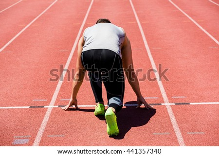 Rear view of determined athlete ready to run on running track