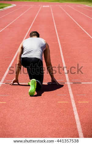 Rear view of determined athlete ready to run on running track - stock photo