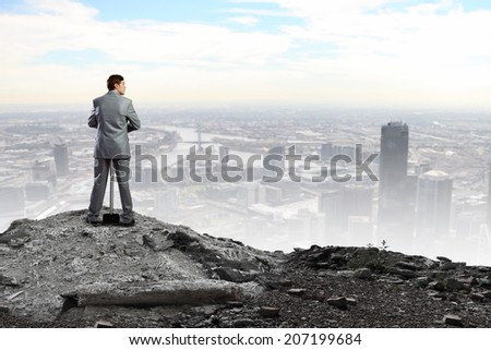 Rear view of determined businessman with big hammer in hands