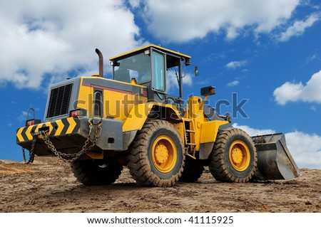 rear view of diesel wheel loader bulldozer with bucket pulled down outdoors - stock photo