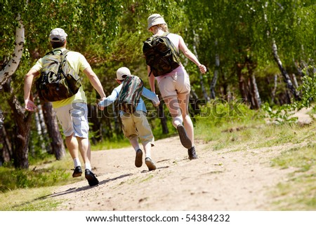 Rear view of dynamic family members running down country road at summer