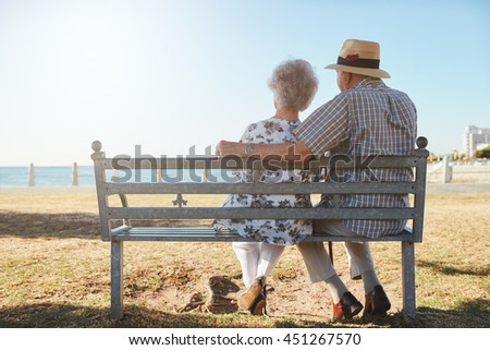 Rear view of elderly couple relaxing on a bench looking out to sea. Senior man and woman sitting on a bench outdoors and enjoying the view. - stock photo