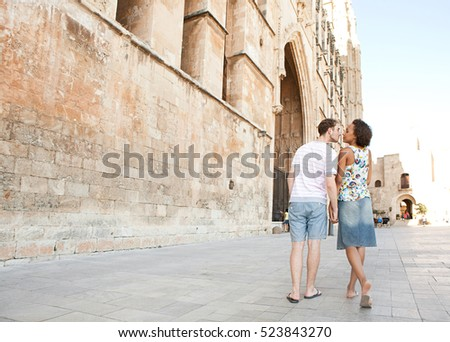 Rear view of ethnically diverse couple walking together by cathedral stone building holding hands, kissing. Monument sightseeing destination, holiday outdoors. Travel lifestyle, tourist recreation.