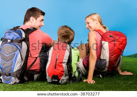 Rear view of family chatting on grassland during rest over blue background - stock photo