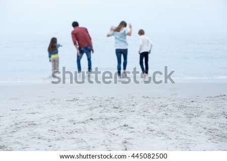 Rear view of family enjoying in shallow water at beach - stock photo
